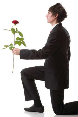 Young man presenting a flower - red rose isolated white background photo