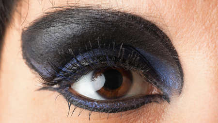 woman Beautiful shape of female eye with black blue cosmetic make-up Professional make up photo