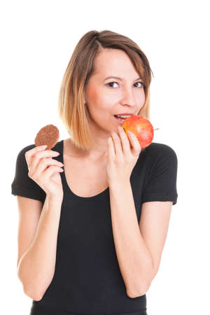 Young beautiful female choose from sweet cake and red apple photo