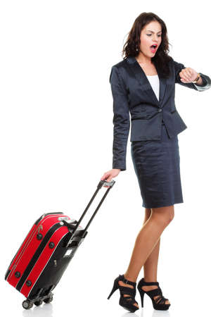 Full length of young business woman to late pulling red travel bag clock isolated on white background photo