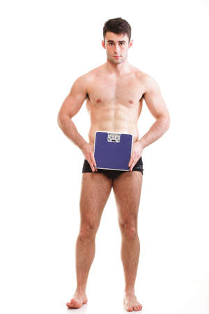 Healthy young man with a weight scale. Isolated over white background photo