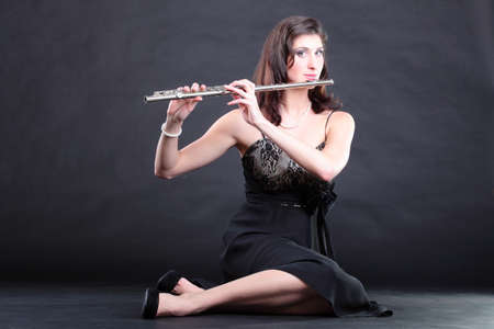 silver flute: girl woman plays the flute on a black background