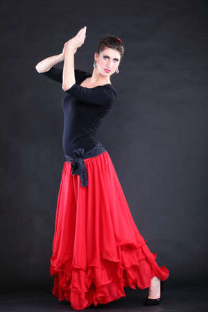 Attractive spanish dancer over black background young woman dancing flamenco photo