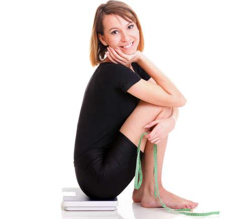 Raza cauc�sica escala de peso de una mujer aislada sobre fondo blanco