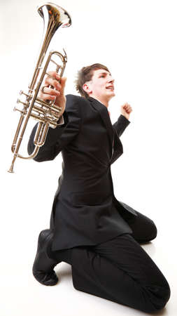 Portrait of a young jazz man joy, glee and his Trumpet white background photo