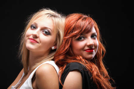 two happy young girlfriends blonde and red-hair black background photo
