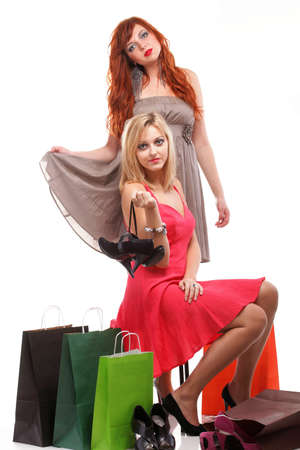 two happy girls ginger and blonde with shopping bags shoes over white photo