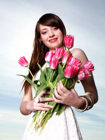 Beautiful young woman with pink tulips bunch of flowers photo