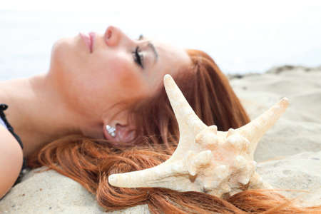 The beautiful girl lies on sea coast with shells nature vacation woman Stock Photo - 13875087