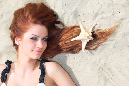 The beautiful girl lies on sea coast with shells nature vacation woman Stock Photo - 13852738