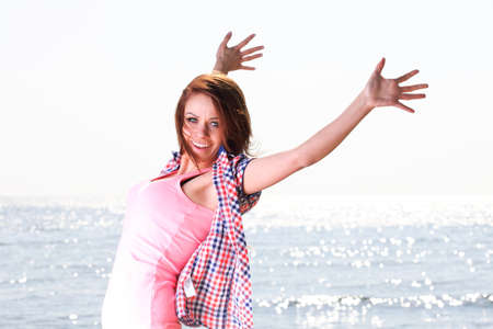 Happiness bliss freedom concept. Woman happy smiling joyful with arms up dancing on beach in summer during holidays travel. Beautiful young cheerful Caucasian female model photo