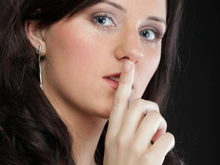 Young girl asking for silence beautiful woman with finger on her lips - copyspace Stock Photo - 14065290