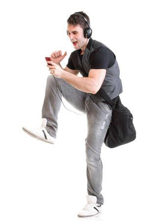 Retrato de cuerpo entero del tel�fono del muchacho de escuela aislado en marcha blanca mientras escucha m�sica Foto de archivo