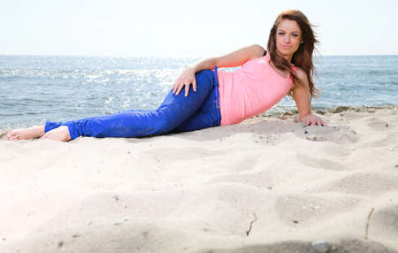 Beach holidays woman enjoying summer sun lie in sand looking happy at copy space. Beautiful young model photo