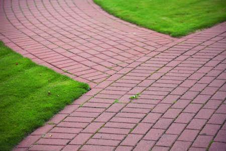 Camino de piedra del jard�n con la hierba que crece entre las piedras y en los alrededores, Acera del ladrillo