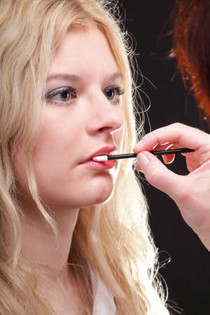Beautiful blonde woman putting on makeup red lipstick photo