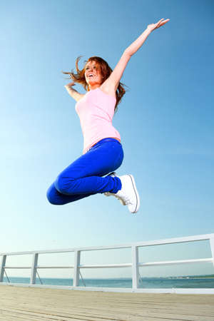 Attractive girl Young woman jumping in the sky Stock Photo - 15043294
