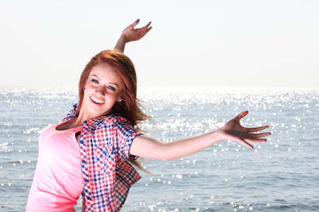 Woman happy smiling joyful with arms up dancing on beach in summer during holidays travel photo
