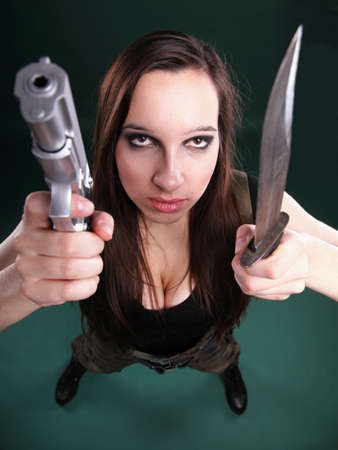 Sexy young woman in red with a gun, knife on green background photo