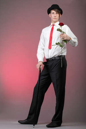 Young men with the red rose on colour background. Love and reflection. photo