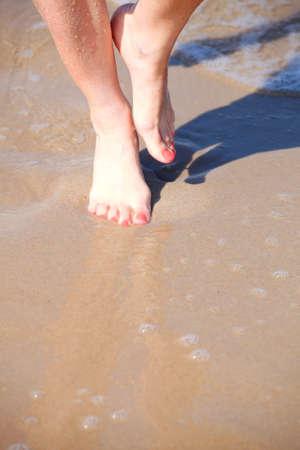 nice legs: nice legs in water, nice pedicure red nail sand beach Stock Photo