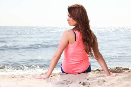 Beach holidays woman enjoying summer sun sitting in sand looking happy at copy space. Beautiful young model photo