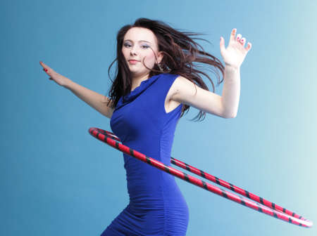 Beautiful woman in a sport wear. Dance hoop gym exercises blue background