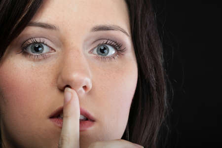 Young girl asking for silence beautiful woman with finger on her lips - copyspace Stock Photo - 15891340