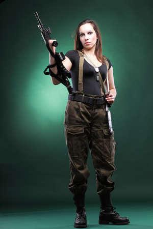 Hermosa mujer joven con rifle de pl�stico Militar del Ej�rcito Holding Gun fondo verde Foto de archivo