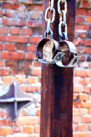 manacles: grilletes, esposas viejas de ladrillo de dos anillos antiguos de hierro oxidado en la pared de fondo Foto de archivo