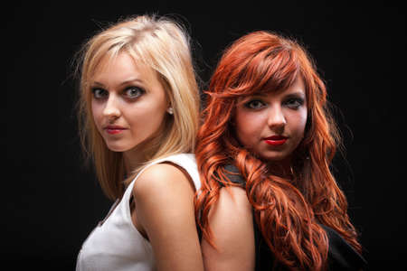 sexy teenage girls: two happy young girlfriends blonde and red-hair black background Glamour