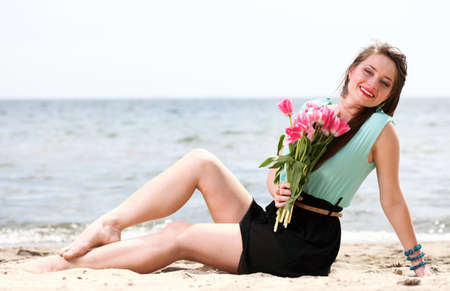 young beautiful woman portrait on the beach bunch flower photo