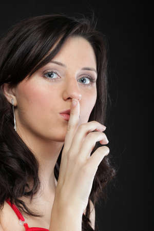 Young girl asking for silence beautiful woman with finger on her lips - copyspace Stock Photo - 16237679