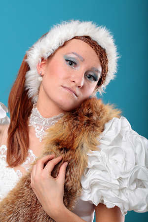 Beautiful ginger in white dress of Snow Queen blue background photo