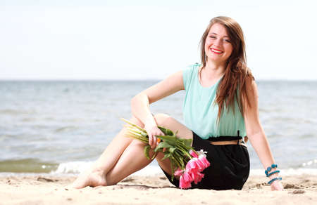 one adult only: young beautiful woman portrait on the beach bunch flower Stock Photo