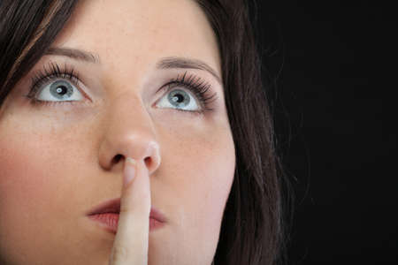 Young girl asking for silence beautiful woman with finger on her lips - copyspace photo