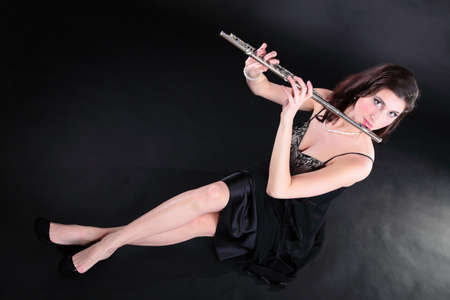 girl woman plays the flute on a black background Stock Photo - 17391079