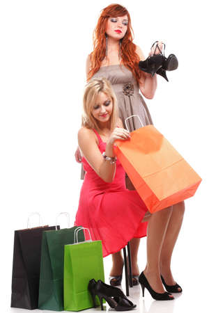 two happy girls ginger and blonde with shopping bags shoes over white Stock Photo - 18474011