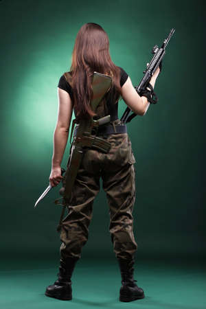 camos: Beautiful woman with rifle plastic Military Army girl Holding Gun green background Stock Photo