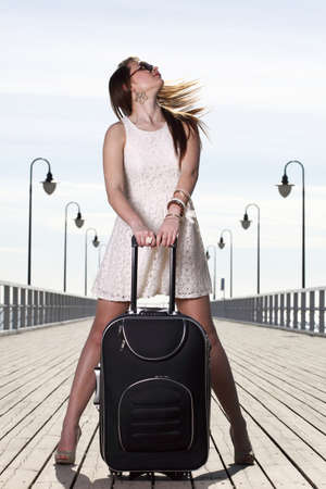 Beautiful woman going on a sea mooring suitcase pier photo