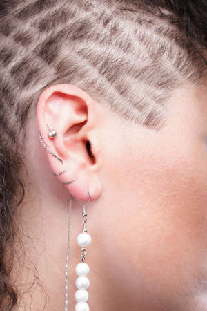 Ear super piercing woman hair background skin photo