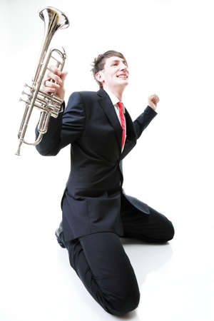 Excited man kneeling with trumpet in hand and screaming. Isolated on white background. photo