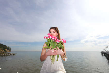 Beautiful young blonde woman with pink tulips blue sea and sky photo