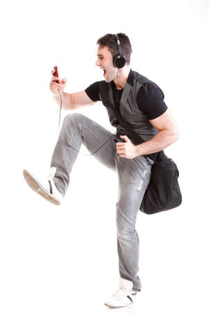 length: Full length portrait school boy phone isolated on white running while listening to music Stock Photo