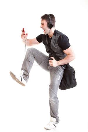 full length: Full length portrait school boy phone isolated on white running while listening to music Stock Photo