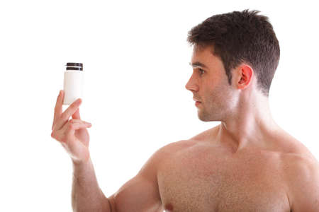 Athletic sexy male body builder holding a boxes with supplements on his biceps, man holding bottle of pills 版權商用圖片