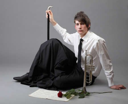 Portrait of a young jazz man andTrumpet grey background. Love melody photo