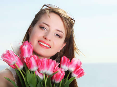 Beautiful young woman with pink tulips bunch of flowers