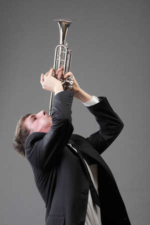 Portrait of a young jazz man playing his Trumpet grey background photo