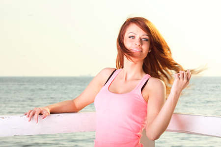 Attractive girl on pier winter in hair Young woman on background of sea sky photo
